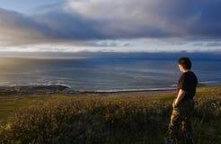 Un hombre se coloca en una roca en la costa ártica Foto de archivo