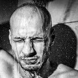 Un hombre se da una ducha fría después de trabajo para calmar abajo después de día frustrado y nervioso duro en su cierre del tra foto de archivo libre de regalías