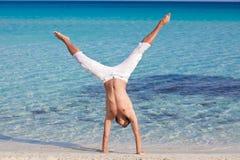 Un hombre se está colocando upside-down en la playa Fotos de archivo libres de regalías