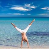 Un hombre se está colocando upside-down en la playa Imagen de archivo