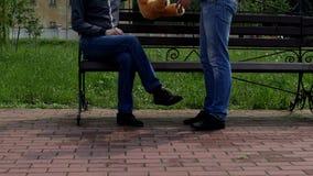 Un hombre se está sentando en un banco, otro hombre se acerca a él y da un oso de peluche, un hombre lo lanza y niega almacen de video