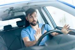Un hombre se está sentando en la rueda del coche Imagen de archivo libre de regalías