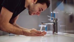 Un hombre se lava las manos y la cara almacen de video