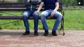 Un hombre se sienta en un banco a él viene y otro hombre se sienta y frota ligeramente su pierna, homosexualidad, acoso metrajes