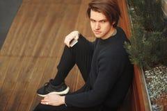 Un hombre se sienta en un banco con un teléfono El hombre de la moda mira en la distancia Hombre de la moda afuera en suéter fotos de archivo libres de regalías