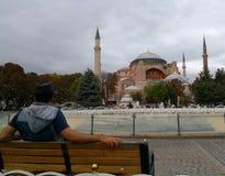 Un hombre se sienta en el banco y las miradas en la mezquita de Hagia Sophia foto de archivo libre de regalías