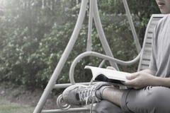 Un hombre se sienta en el oscilación y la lectura de un libro para el presentatio de la bandera Fotografía de archivo