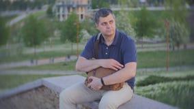 Un hombre se sienta en el parque y firmemente agarrar un bolso llenado del dinero almacen de metraje de vídeo