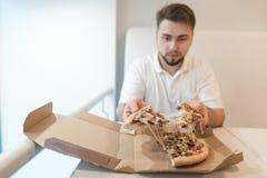 Un hombre se sienta en la tabla cerca de la caja y los controles en el suyo dan algunos pedazos de pizza El hombre come una pizza Imagen de archivo
