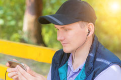 Un hombre se sienta en un parque y mira en el teléfono Imágenes de archivo libres de regalías