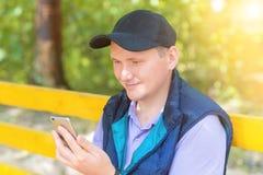 Un hombre se sienta en un parque y mira en el teléfono Fotos de archivo libres de regalías