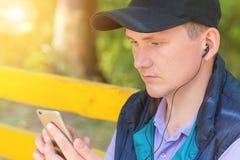 Un hombre se sienta en un parque y mira en el teléfono Imagenes de archivo