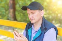 Un hombre se sienta en un parque y mira en el teléfono Foto de archivo