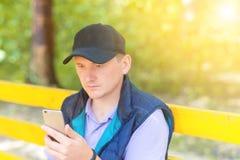 Un hombre se sienta en un parque y mira en el teléfono Imagen de archivo libre de regalías