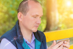 Un hombre se sienta en un parque y mira en el teléfono Fotografía de archivo libre de regalías