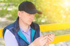 Un hombre se sienta en un parque y mira en el teléfono Fotos de archivo