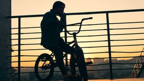 Un hombre se sienta en una bici en un fondo de la puesta del sol Silueta activa del adolescente metrajes