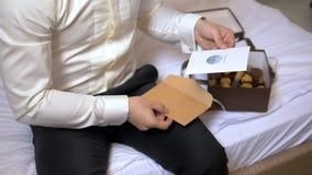 Un hombre se sienta en una cama en hoteles y lee una letra de un sobre almacen de metraje de vídeo