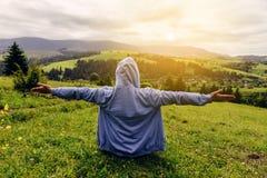 Un hombre se sienta en una colina de la montaña, sus manos miran la visión desde arriba y disfrutan de la libertad y del logro de Fotos de archivo libres de regalías