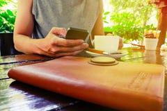 Un hombre se sienta en una silla en cafetería y envío de mensajes de texto con ella Imagen de archivo libre de regalías