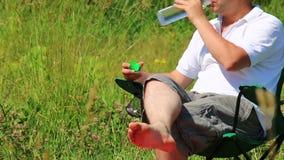 Un hombre se sienta en una silla plegable de la comida campestre y bebe el agua Cierra la botella y la pone en el soporte almacen de video