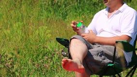 Un hombre se sienta en una silla plegable de la comida campestre y bebe el agua Cierra la botella y la pone en el soporte almacen de metraje de vídeo