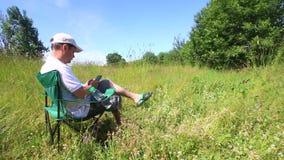 Un hombre se sienta en una silla plegable de la comida campestre y trabaja con un smartphone Alrededor está agitando la hierba, i metrajes