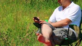 Un hombre se sienta en una silla plegable y juegos de la comida campestre en el smartphone Después él se levanta y se va almacen de video