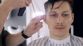 Un hombre se sienta mientras que se cortan sus lados del pelo metrajes