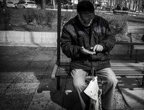Un hombre se sienta y cuenta su dinero pasado un hombre pobre y parado Uso editorial solamente Burgas/Bulgaria/03 08 2017 imagenes de archivo