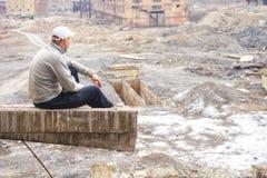 Un hombre se sienta y mira de una altura las ruinas de una planta del cinc, edificios de ladrillo destruidos, los restos de las p fotografía de archivo