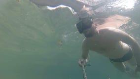 Un hombre se zambulle y hace un selfie debajo del agua metrajes
