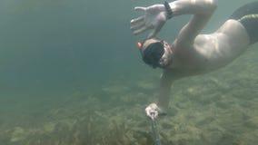 Un hombre se zambulle y hace un selfie debajo del agua agitar su mano a usted metrajes