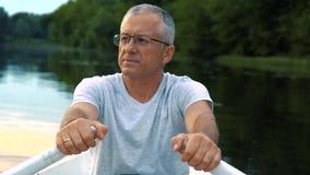 Un hombre serio canoso delgado en una camiseta gris y los vidrios que reman en un barco blanco en un río tranquilo en un verano almacen de metraje de vídeo
