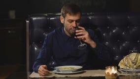Un hombre serio come en el restaurante y bebe el vino con el almuerzo almacen de metraje de vídeo