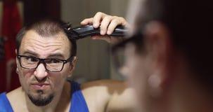 Un hombre serio con los vidrios mira en el espejo y afeita el pelo en su cabeza con un condensador de ajuste profesional almacen de metraje de vídeo