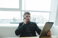 Un hombre serio mira la tableta y habla por el teléfono en un café para una taza de café Un hombre de negocios goza de los artilu Fotos de archivo