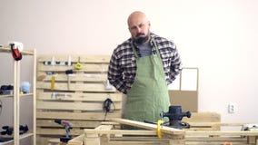 Un hombre severo de aspecto caucásico con una barba gruesa rueda sus mangas de la camisa antes del trabajo próximo almacen de video
