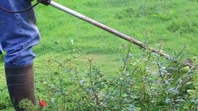Un hombre siega la hierba en el césped cerca de la casa almacen de metraje de vídeo