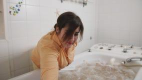 Un hombre sienta en los aceites de ba?o medicinales, empleado de la muchacha en un balneario, consiguiendo un masaje de la agua c almacen de video