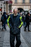 Un hombre sin hogar cubierto adentro babea y la suciedad camina a través de las calles de Praga en un día de primavera frío imagen de archivo