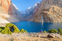 Un hombre solitario se sienta en el banco del lago hermoso de la montaña Imagenes de archivo