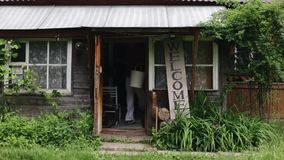 Un hombre sonriente joven con dos cubos vacíos que sale fuera de la pequeña casa de madera En el pueblo Muestra agradable vacío metrajes