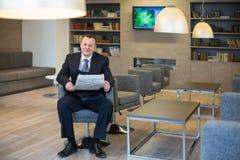Un hombre sonriente que lee un periódico Fotos de archivo libres de regalías