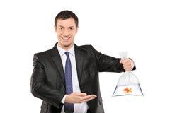 Un hombre sonriente que muestra una bolsa de plástico con los pescados Imagen de archivo