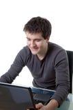 Un hombre sonriente que trabaja con una computadora portátil Fotografía de archivo libre de regalías