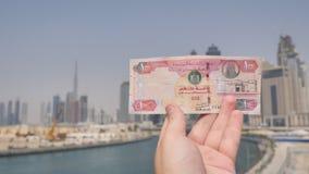 Un hombre sostiene un billete de banco de 100 dirhames en las manos de la ciudad de Dubai Dinero de los United Arab Emirates almacen de video