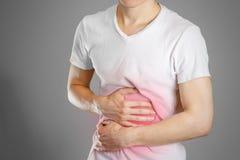 Un hombre sostiene el estómago El dolor en su ardor de estómago del pecho Foto de archivo