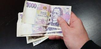 Un hombre sostiene en mano derecha al manojo de dinero checo foto de archivo