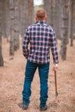Un hombre sostiene un hacha en su mano bajada abajo en el bosque del otoño Imagenes de archivo